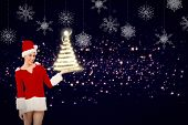 Pretty santa girl presenting with hand against hanging snowflakes