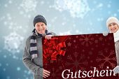 Winter couple showing poster against gift card with festive bow