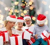 family, happiness, generation, holidays and people concept - happy family in santa helper hats with gift boxes sitting over christmas tree lights background