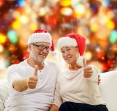 family, holidays, christmas, age and people concept - happy senior couple in santa helper hats sitting on sofa over red lights background and showing thumbs up gesture