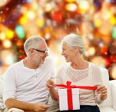 family, holidays, christmas, age and people concept - happy senior couple with gift box over red lights background