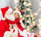 holidays, celebration, childhood and people concept - smiling little girl hugging with santa claus over christmas tree lights background