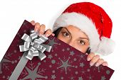 Woman looking towards the camera against christmas wrapping paper with bow