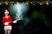Pretty santa girl presenting with hands against fir branch christmas decoration garland