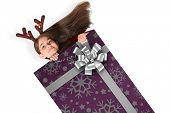 Festive little girl showing card against christmas wrapping paper with bow