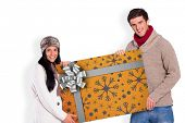 Young couple holding a poster against christmas wrapping paper with bow
