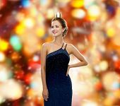 people, holidays, royalty and glamour concept - smiling woman in evening dress wearing golden crown over red lights background
