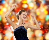 people, party, holidays and glamour concept - smiling woman dancing with raised hands over red lights background