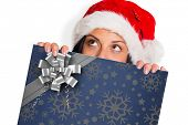 Woman looking away from camera against christmas wrapping paper with bow