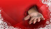 Hand bursting through paper against christmas themed snow flake frame