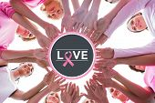 Happy women in circle wearing pink for breast cancer against breast cancer awareness message on poster
