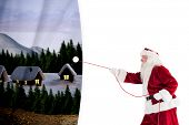 Santa pulls something with a rope against white curtain blind