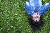 Girl in a denim jacket lying on the grass (with space for text)