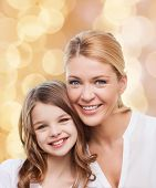 family, childhood, happiness and people - smiling mother and little girl over beige lights background