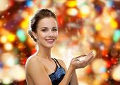 people, holidays and glamour concept - smiling woman in evening dress with diamond over red lights background