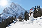 Snowman against Alpine panorama. Switzerland