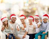 family, generation, gesture, holidays and people concept - happy family in santa helper hats showing thumbs up over lights background