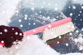transportation, winter, weather, people and vehicle concept - closeup of woman cleaning snow from car windshield with brush