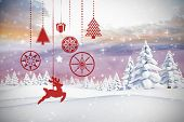 Hanging red christmas decorations against twinkling stars