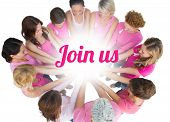 Cheerful women joined in a circle wearing pink for breast cancer on white background