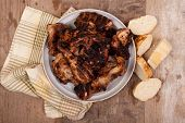 foto of jerk  - grilled jerk chicken in the clay bowl on wooden table - JPG