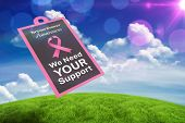 Breast cancer awareness message against green field under blue sky