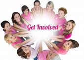 Cheerful women joined in a circle and looking up at camera wearing pink for breast cancer on white background