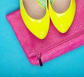 Neon high heels and snakeskin print bag, woman fashion concept