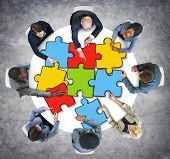 Group of Business People with Jigsaw Puzzle in Photo and Illustration