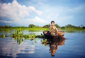 foto of fine art portrait  - Cambodian boy travelling by boat in his floating village Cambodia - JPG