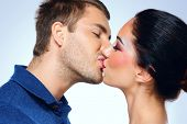 Young couple of lovers kissing isolated on blue background