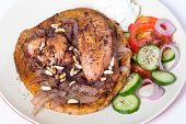 Musakhan, traditional Palestinian sumac chicken, on a plate with a salad and yoghurt,high angle
