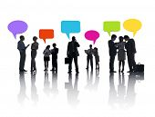 Business People Discussing And Multi-Colored Speech Bubbles Above Them.