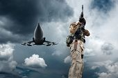 Soldier and military airplane at flying under sky