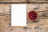 Fresh Wild Berries With Paper Notebook On Wooden Table.