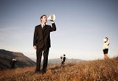 Business people shouting through paper megaphone