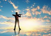 Silhouette of man playing violin high in sky