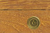 Closeup of cracked wooden drawer with locked key
