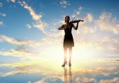 Silhouette of woman playing violin at sunrise