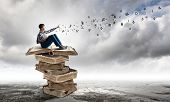 Teenager sitting on pile of books and reading