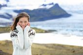 Asian woman portrait by glacier on Iceland wearing Icelandic sweater. Hiker tourist girl smiling cute in nature by glacial lagoon / lake of Fjallsarlon, Vatna glacier, Vatnajokull National Park.
