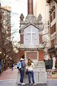 tourists looking at christian monument in city