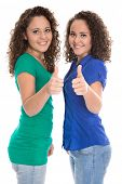 Pretty isolated young girls in blue and green with thumbs up: real twins.