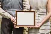 Married couple holding advertising or message board in hands.