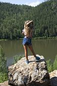 girl standing on a rock and enjoying river  view