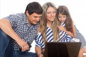 Family sitting on a rug and using a laptop
