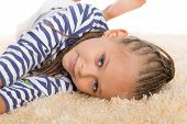 Charming little girl with dreadlocks lays on the mat. Girls six years.