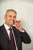 Brazilian man holding a cigar and smiling