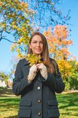 Pretty Lady in Autumn Fashion Outfit Holding Dry Leaves. Captured Outdoor with Grassy Landscape  Leafy Trees and Light Blue Sky Background.