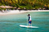 Young man at tropical beach paddling on stand up board